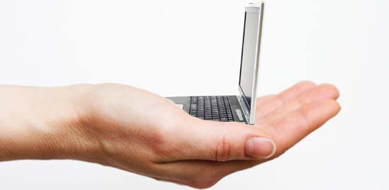 A persons hand holding a miniture size laptop.